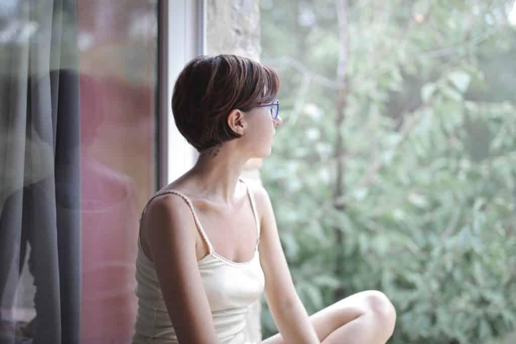 Mulher de óculos e cabelos curtos sentada, vista de perfil, olhando pela janela.
