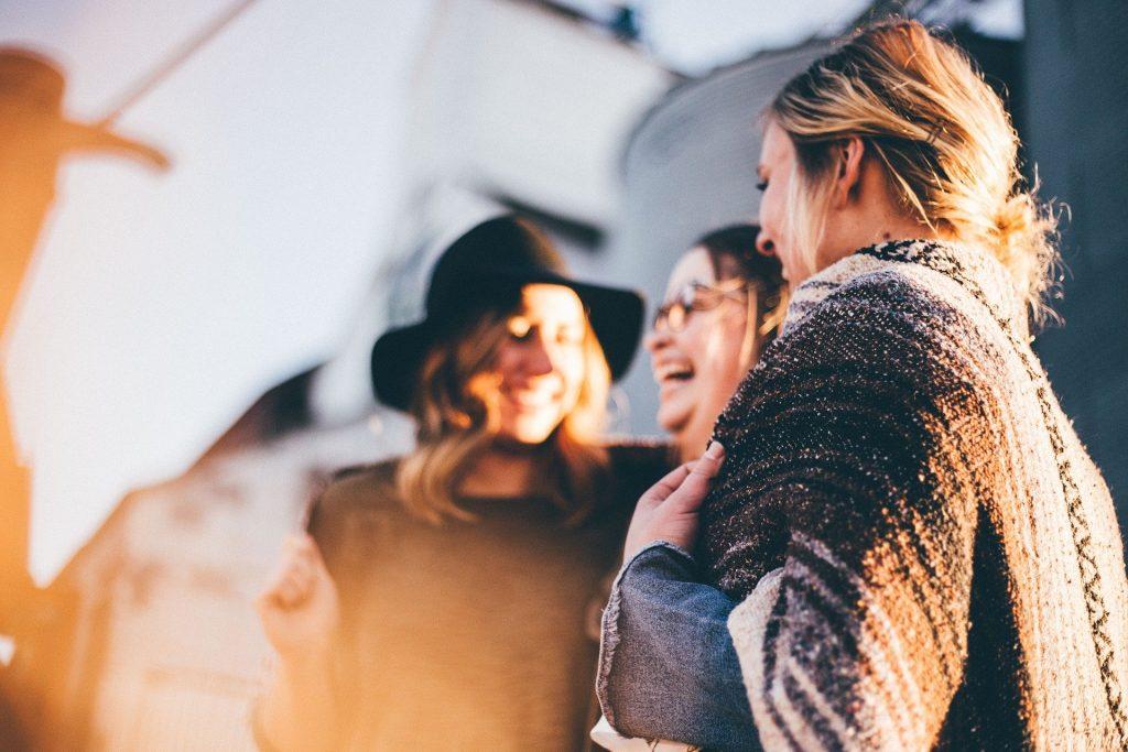 Imagem de 3 mulheres em uma roda, conversando e rindo. Elas estão muito felizes.