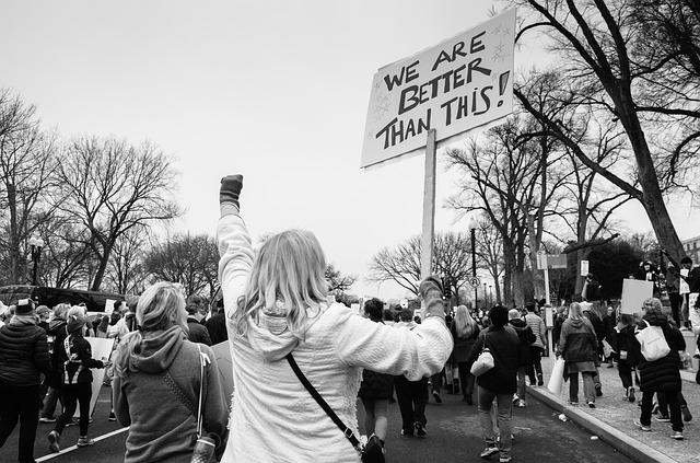 Mulher de costas com placa em protesto