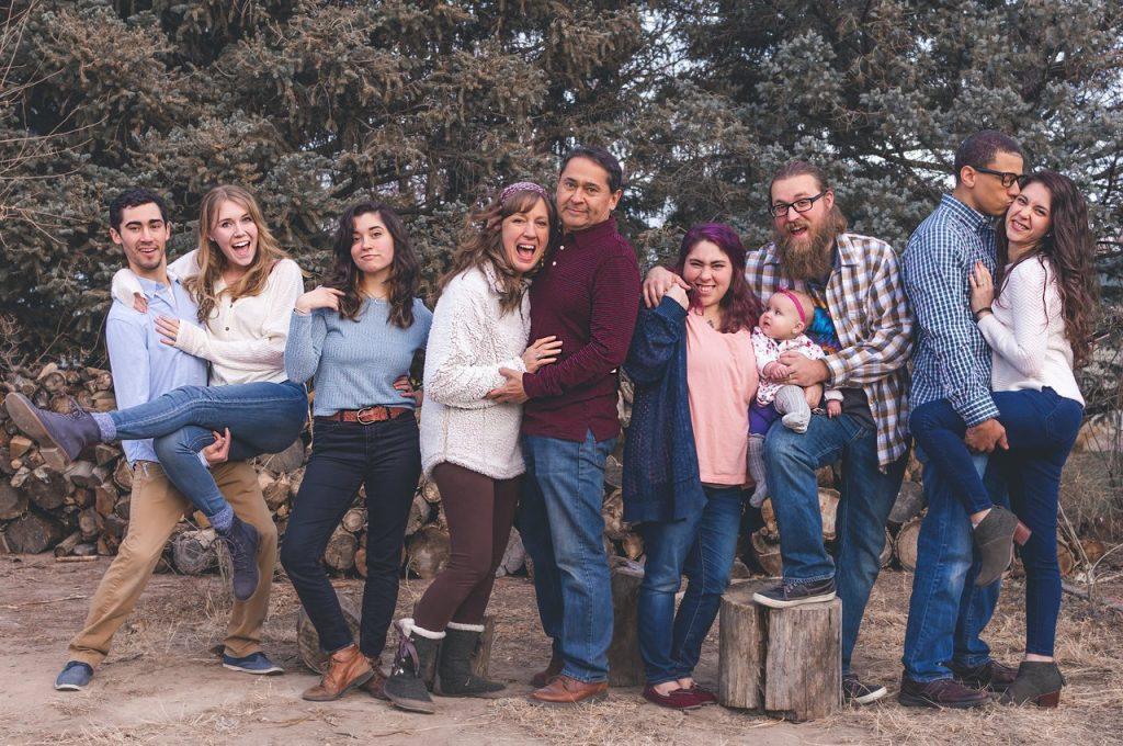Foto de uma família reunida em um parque com árvores, com todos os membros lado a lado, sorrindo e se abraçando.