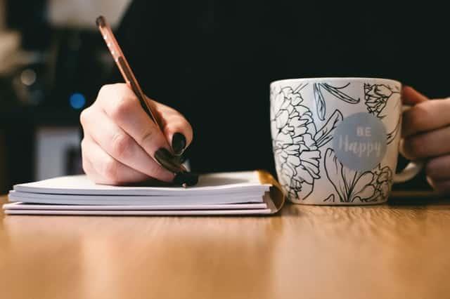 Mulher escrevendo em caderno com caneca ao lado
