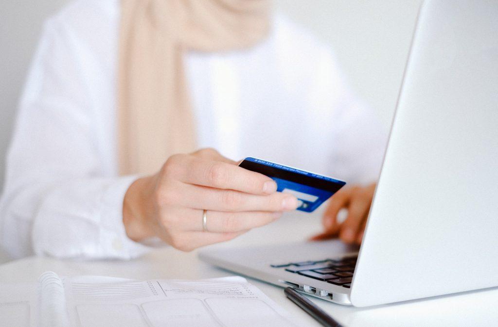 Pessoa segurando um cartão de crédito enquanto usa seu computador.