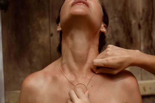 Mulher com cabeça para cima com foco na garganta e outra mexendo em seu colar