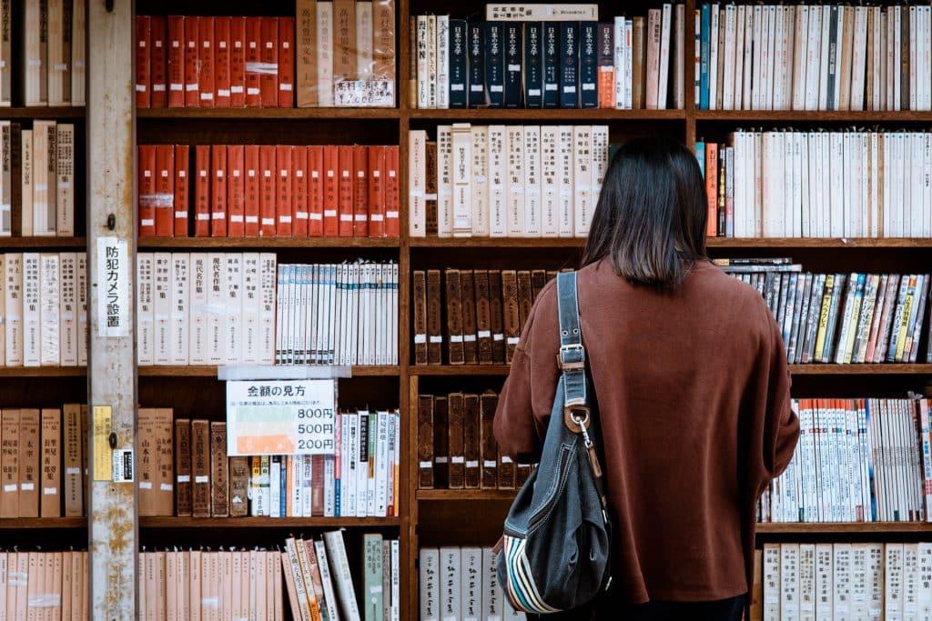 Mulher de costas numa biblioteca