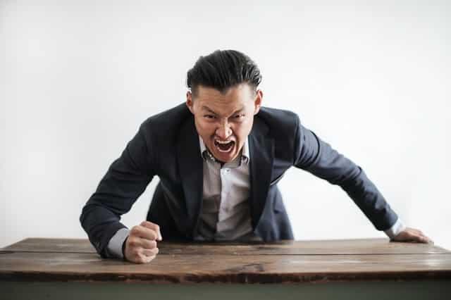 Homem com raiva batendo na mesa de madeira
