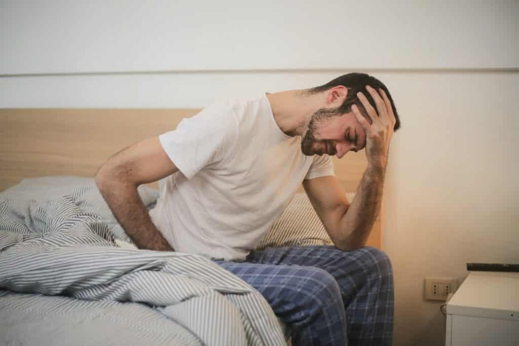 Homem de pijama sentado na cama com a mão sobre a testa e expressão de dor.