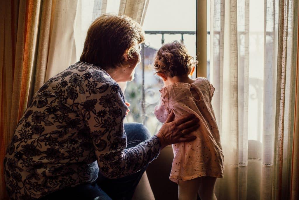 Avó e neta brancas de costas olhando pela janela.