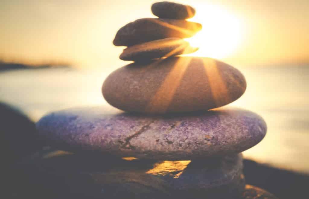 Pedras empilhadas numa praia com luz do sol iluminando