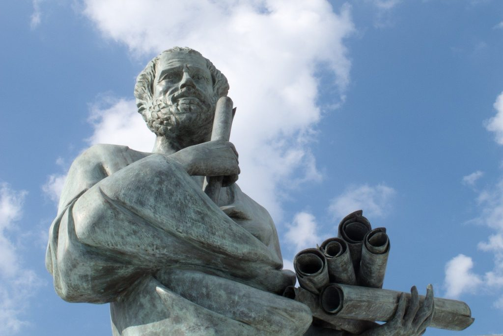 Foto de uma estátua do filósofo da Grécia Antiga Sócrates, sob o céu ensolarado.
