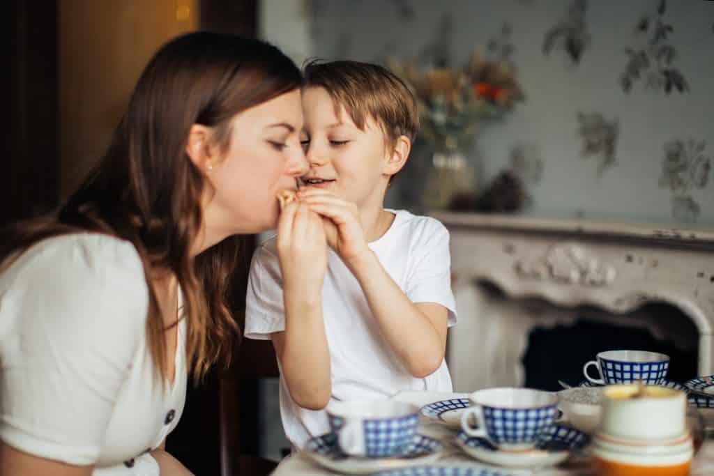 Foto de um menino rindo enquanto dá comida a sua mãe, com ambos sentados à mesa.