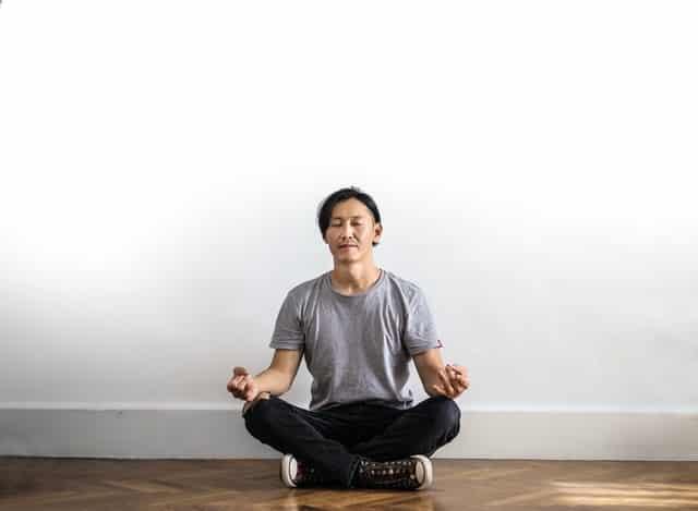 Homem sentado em posição de lótus de olhos fechados meditando
