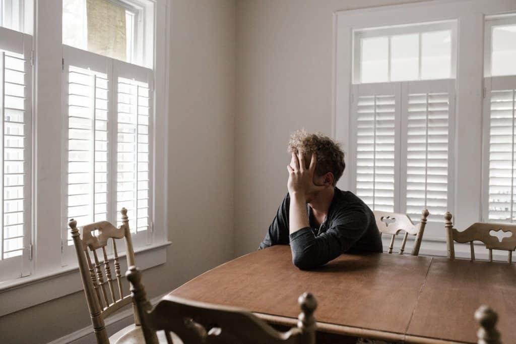 Homem sentado à mesa, em frente à janela, com as mãos segurando o rosto.