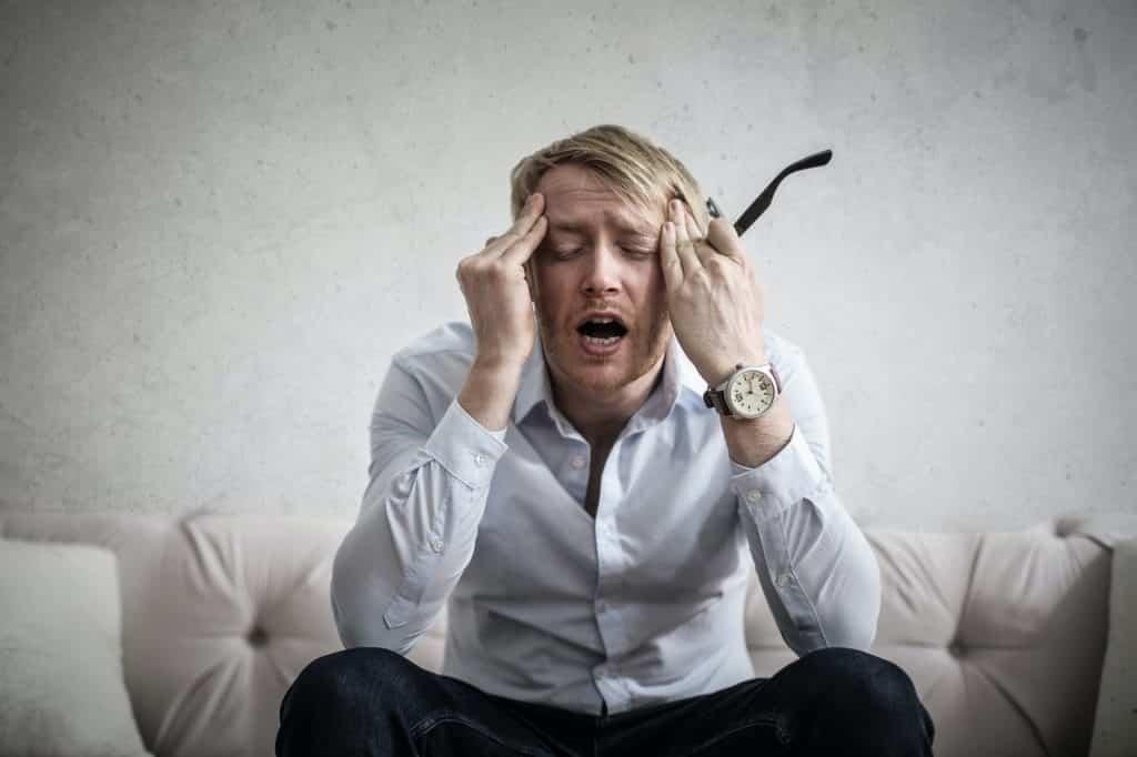 Homem com expressão frustrada, com as mãos sobre as têmporas, sentado no sofá.