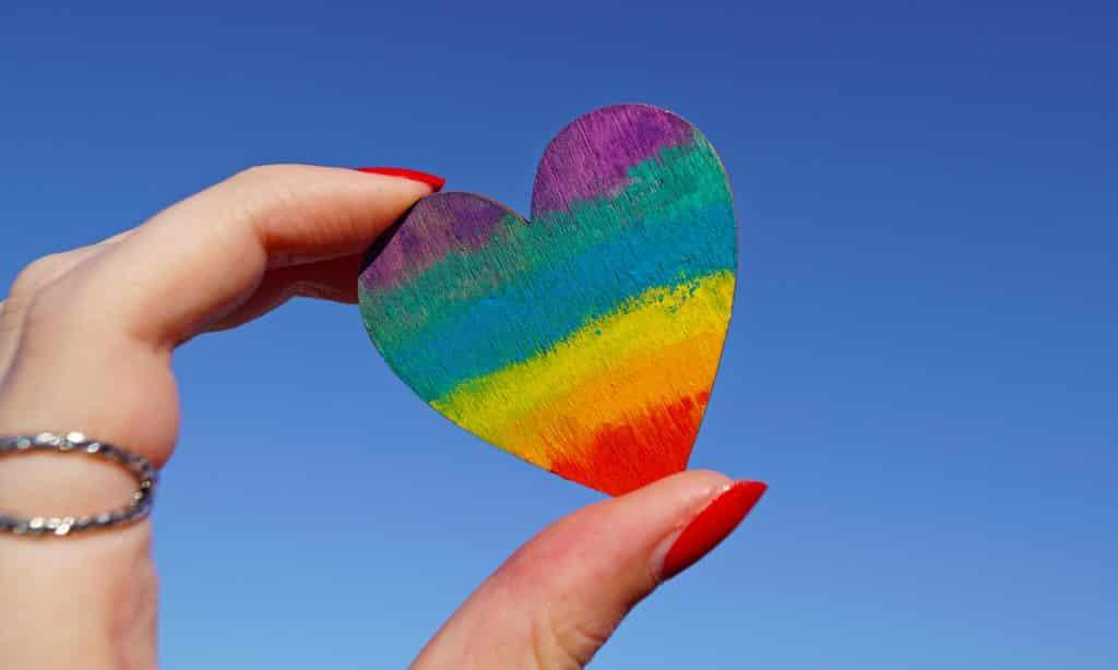 Mão segurando um pedaço de madeira em formato de coração, sob o céu ensolarado.
