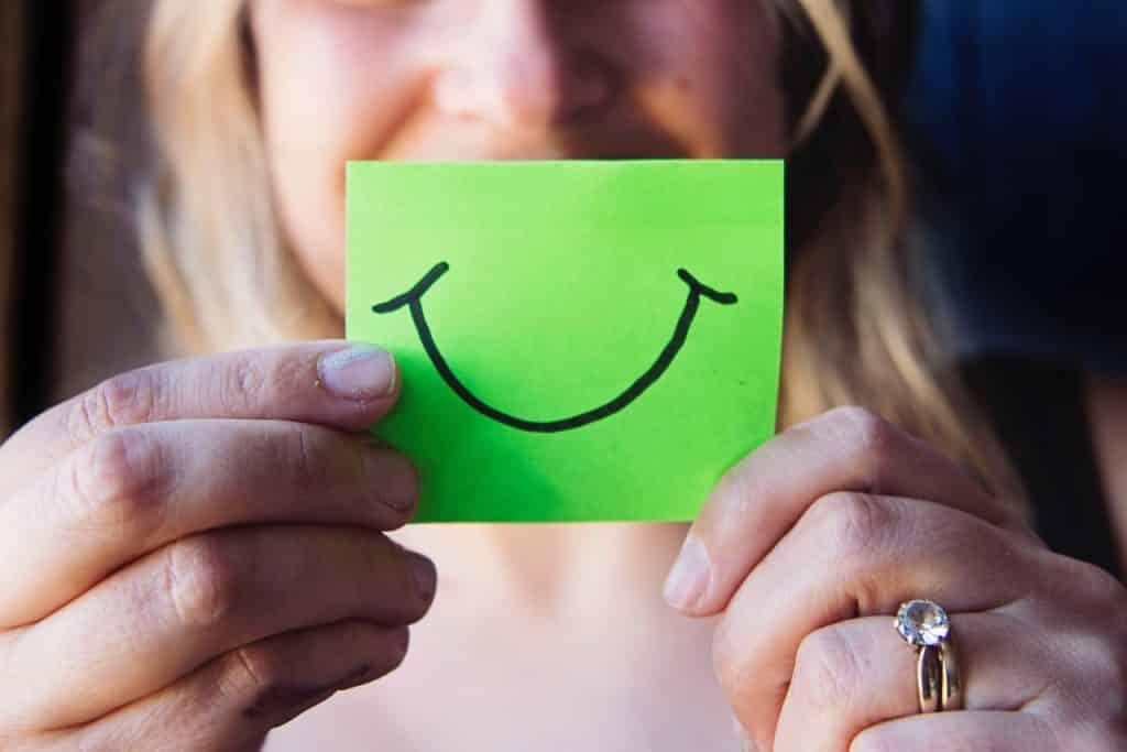 Mulher segurando um papel com um sorriso desenhado à frente de sua boca.