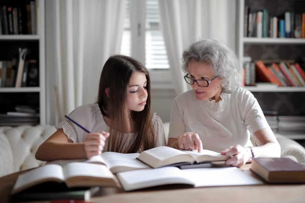 Avó ajudando sua neta com a lição de casa.
