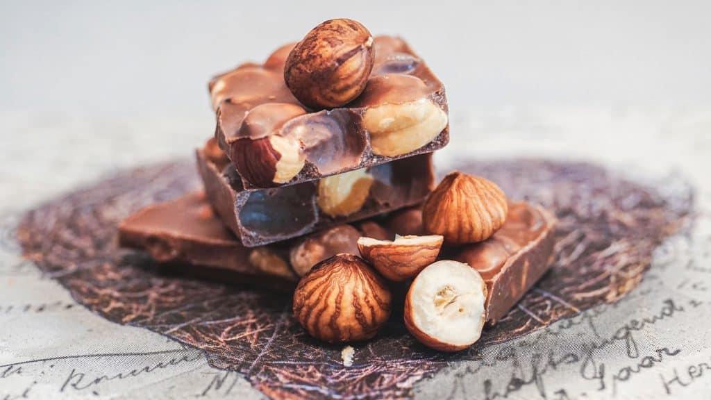 Foto de avelãs em cima de uma barra de chocolate.