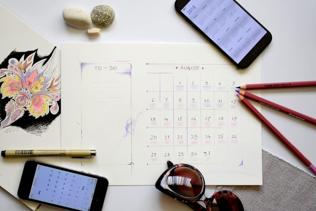Imagem de uma folha de planejamento mensal. Sobre ela três lápis, uma caneta, um óculos escuro, uma calculadora e um celular. Tudo pronto para o planejamento do ano novo.