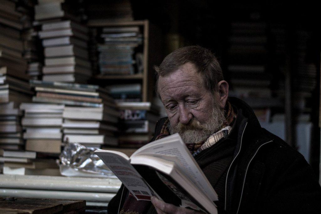 Imagem de um homem na terceira idade lendo o livro sobre Kepler. Ee está em uma biblioteca.