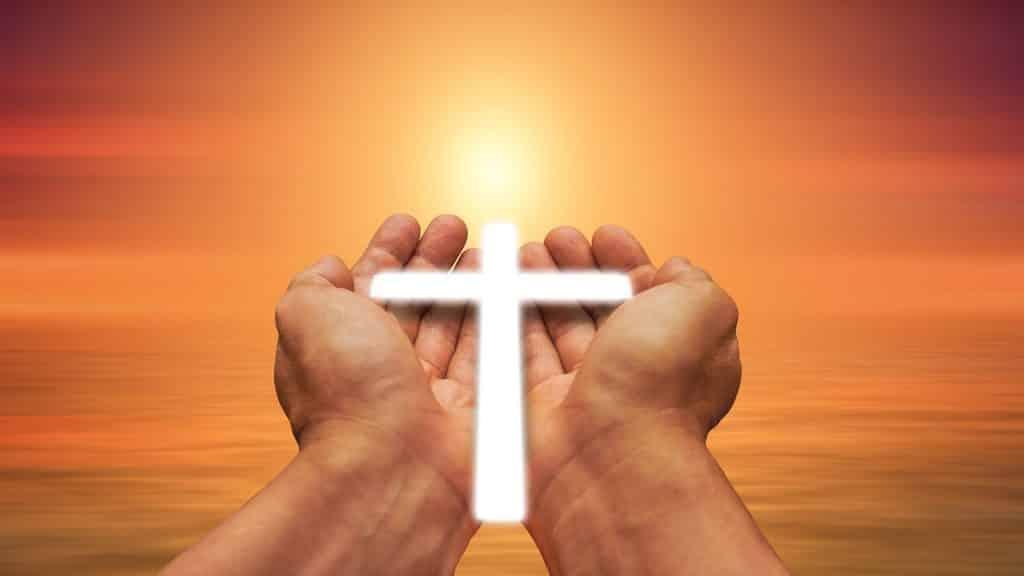 Imagem de duas mãos segurando uma pequena cruz iluminada. Ao fundo a imagem do sol bem alaranjado, representando a oração do perdão.