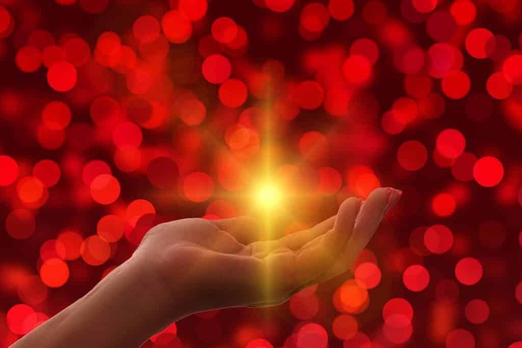 Imagem de uma mão feminina e ao centro uma luz amarela. A imagem tem um fundo iluminado com bolas vermelhas, representando a oração do perdão.