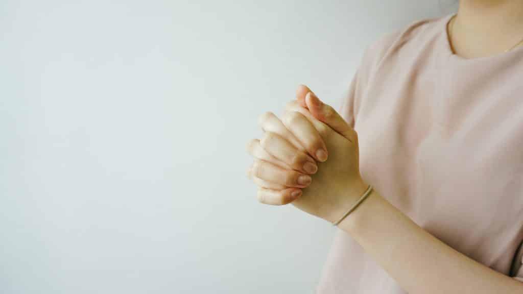 Mulher em pé com as mãos unidas