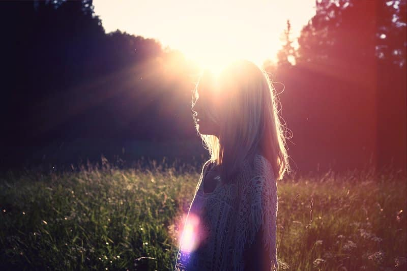 Mulher branca loira meio ao campo com seu rosto coberto pela luz do sol