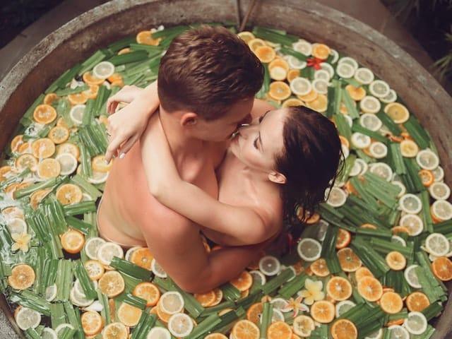 Casal abraçado se beijando em ofurô com folhas e rituais