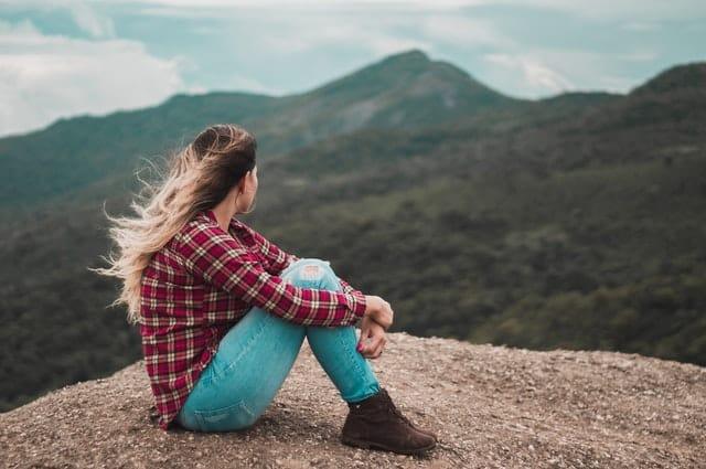 Mulher sentada em pedra com cabelos ao vento