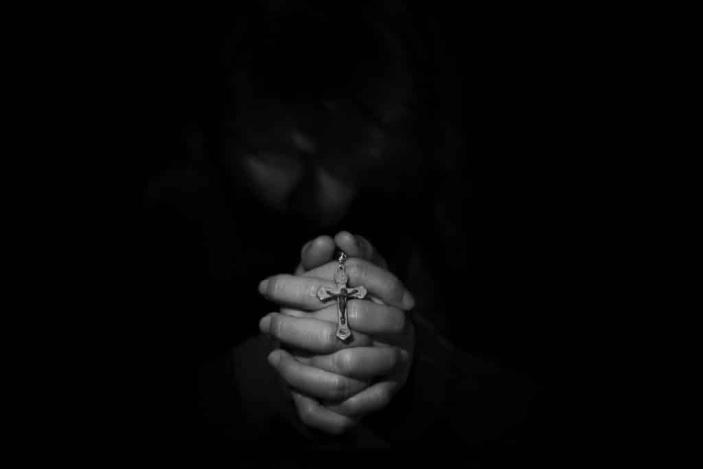 Imagem com fundo preto de uma mão feminina em posição de oração. Ela segura entre as mãos um crucifixo. Ela está fazendo a oração do perdão.