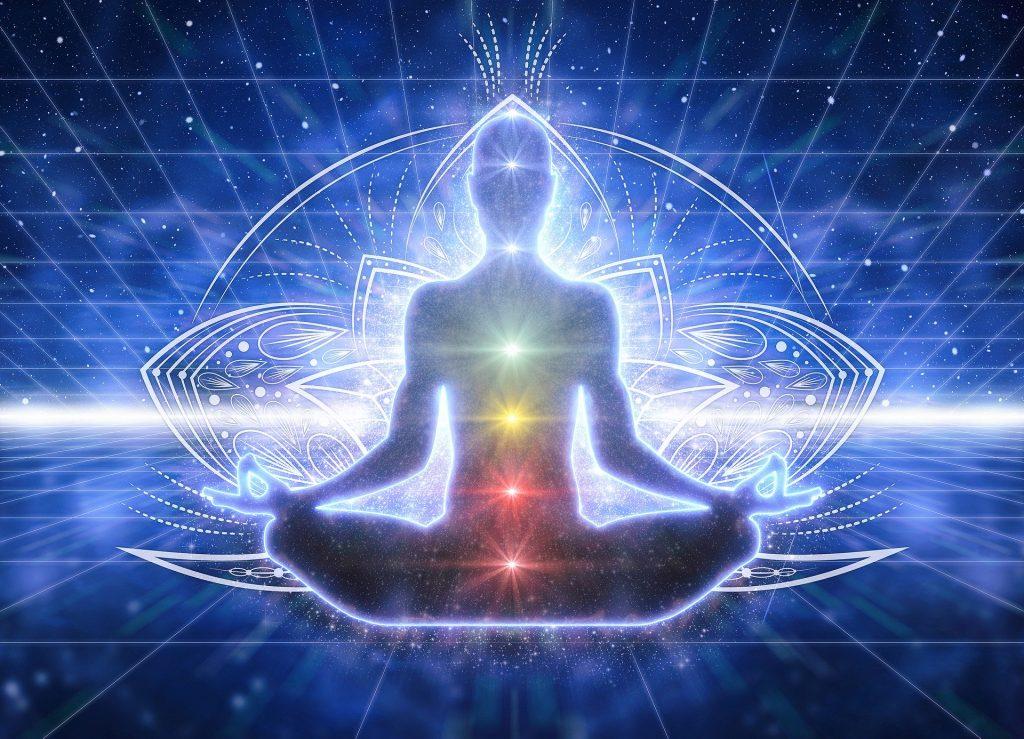Imagem de uma silhueta em posição de meditação. Ao centro do seu corpo as cores que representam os nossos sete chakras.