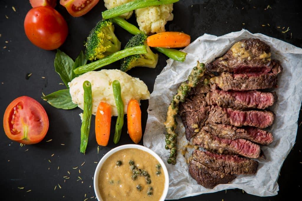 Foto de um pedaço de carne vermelha grelhada com  vegetais ao seu lado.