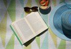 Imagem de um livro, óculos e chapéu de sol e um pote com maça cortada. Elementos que ajudam acalmar a mente e relaxar.