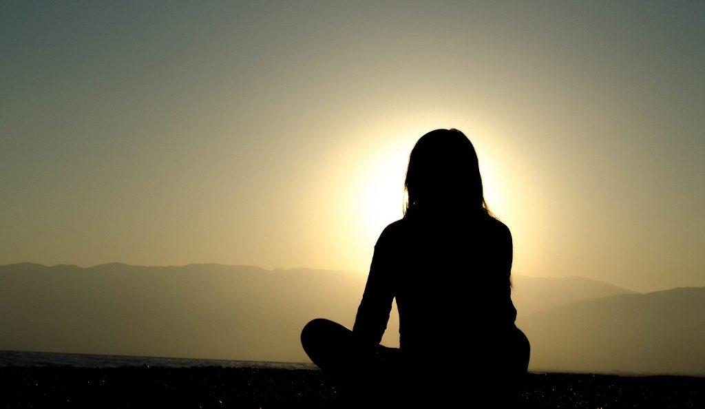 Imagem da silhueta de uma menina em posição de meditação. Ao fundo o por do sol.
