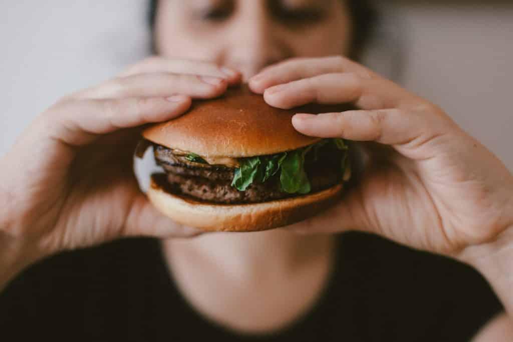 Mulher comendo um hambúrguer com carne e rúcula.