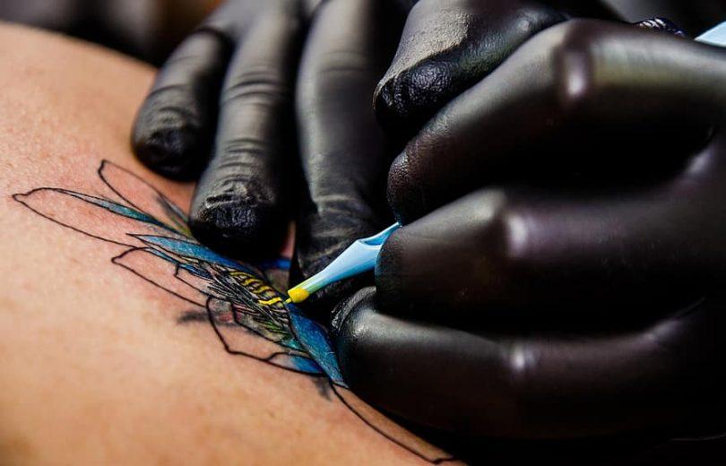 Tatuador preenchendo a figura de uma flor de lótus na pele de uma pessoa.