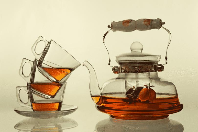 Imagem de uma chaleira de vidro moderna e ao lado três xícaras de vidro uma sobre a outra. A chaleira está com Chá caseiro para dor de estômago.