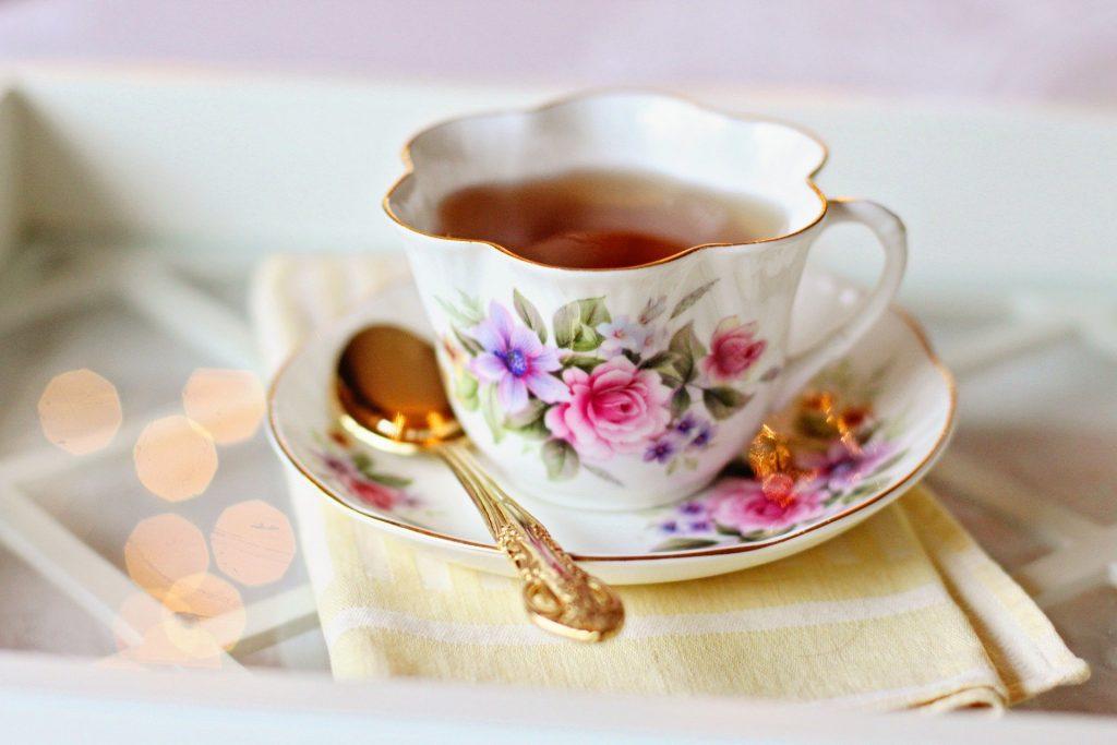 Imagem de uma linda xícara de porcelana pintada com rosas sobre um pires. Ela está cheia de Chá caseiro para dor de estômago.