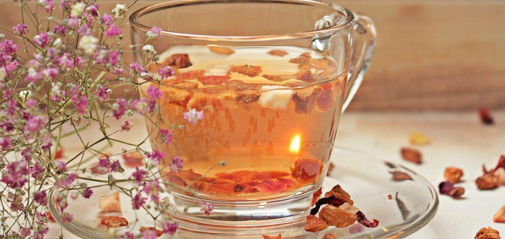 Imagem de uma xícara de vidro sobre o pires e ao lado um lindo ramo de pequenas flores nas cores rosa e branco. A xícara está com Chá caseiro para dor de estômago.