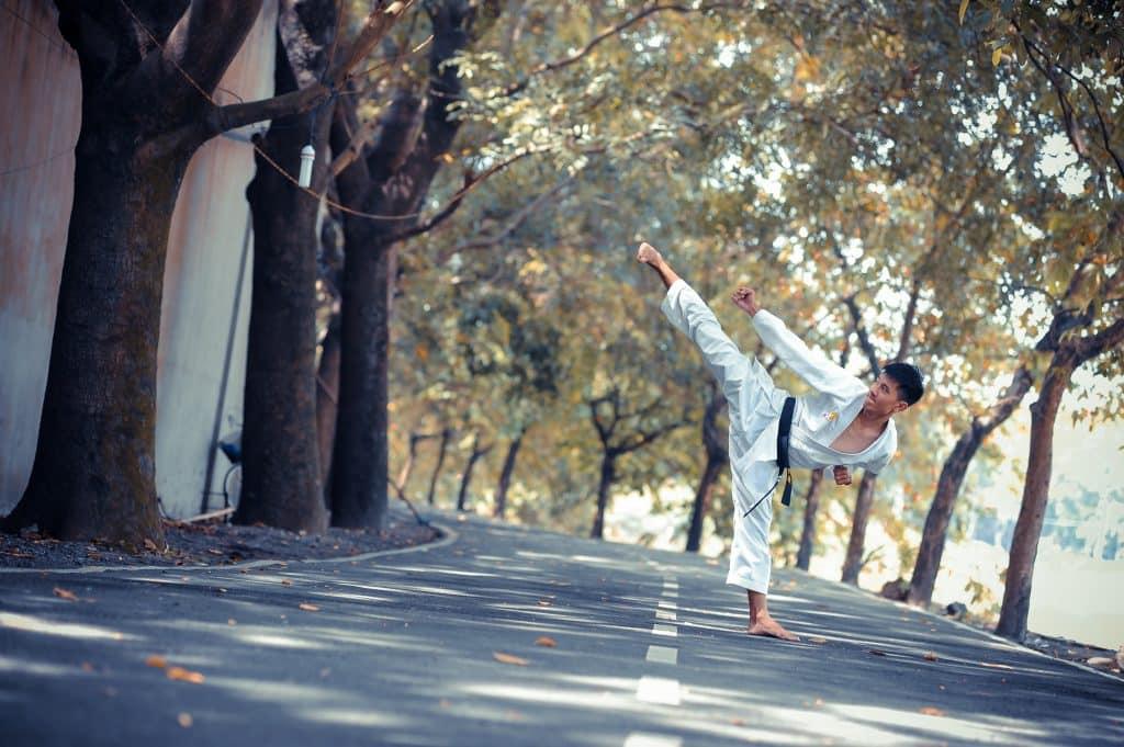 Homem no meio da rua fazendo posição de artes marciais