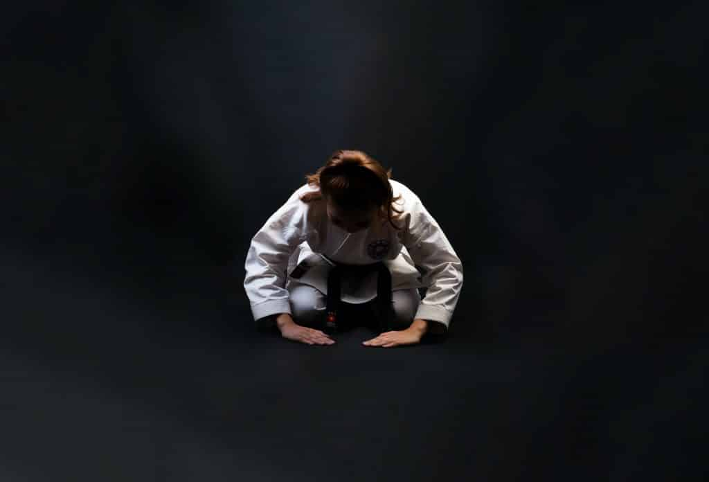 Homem agaixado fazendo uma posição de artes marciais