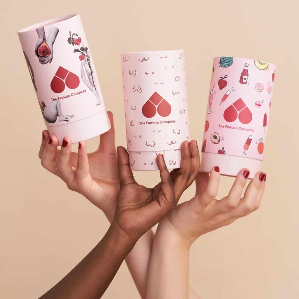 Três mãos femininas segurando um pote cor de rosa com desenhos vermelhos.