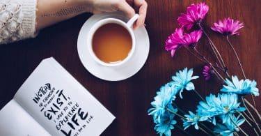 Mulher segurando xícara de chá na mesa ao lado de um livro e algumas flores