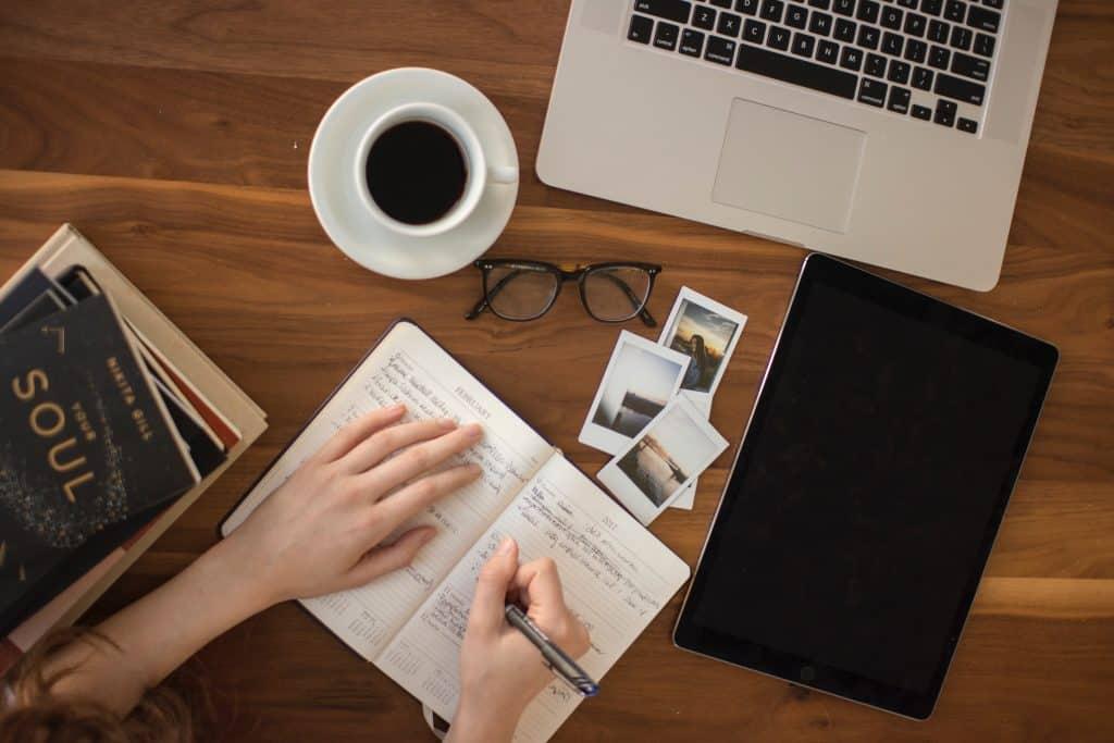 Mulher escrevendo em um caderno ao lado de alguns livros, notebook , fotos e xícara de café