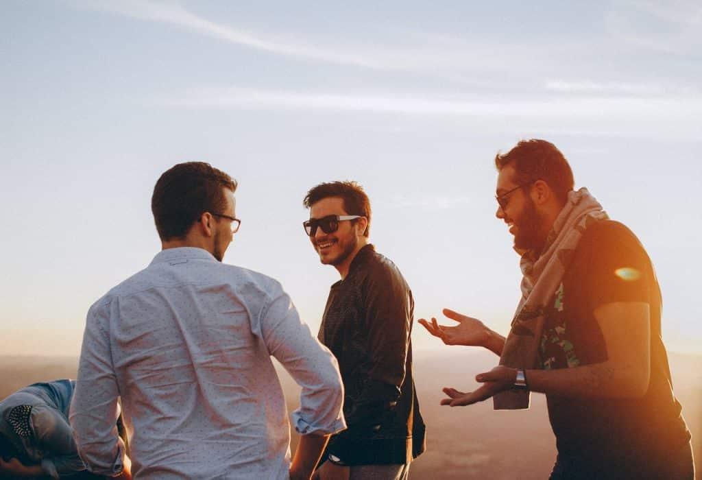 Três homens caminhando e conversando ao pôr do sol.