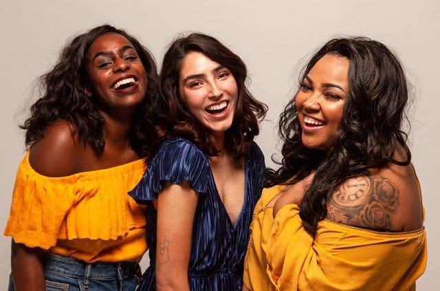 Três mulheres unidas sorrindo