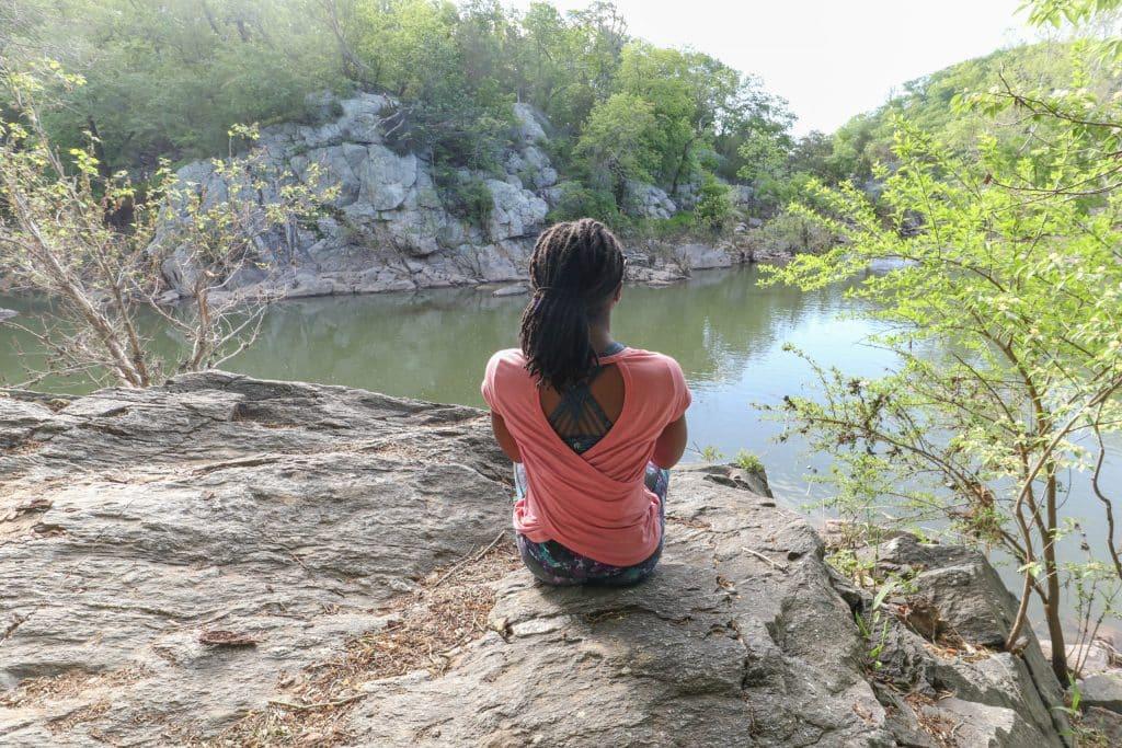 Mulher negra sentada em uma rocha em frente a um lago.