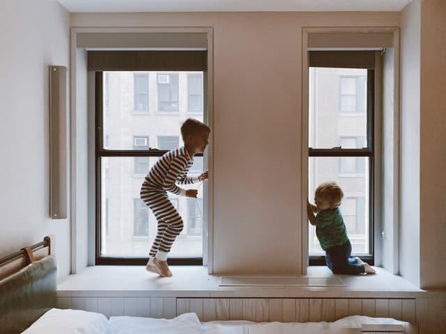 Irmãos brincando perto de janelas fechadas em quarto