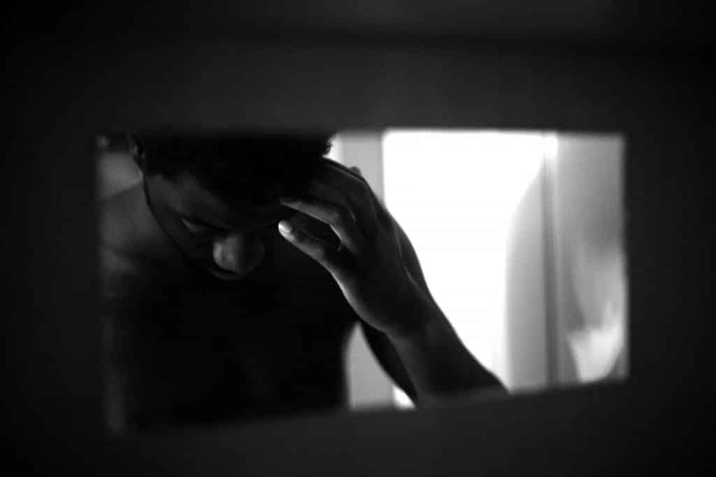 Homem negro visto no reflexo de um espelho, olhando para baixo, com a mão sobre a testa.