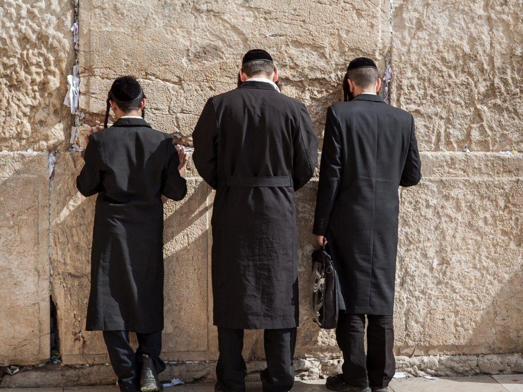 Imagem de três judeus orando no muro das lamentações. Os três estão fazendo a oração do perdão.